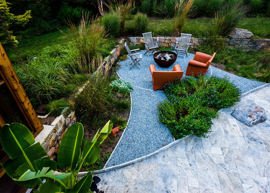 Stone Fire Pit Circle With Plantings And Colored Furniture